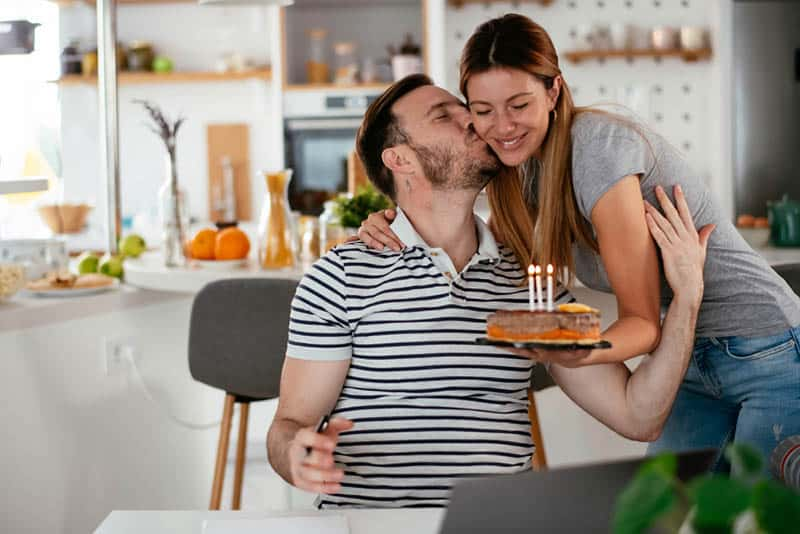 husband kissing his wife for a birthday surprise