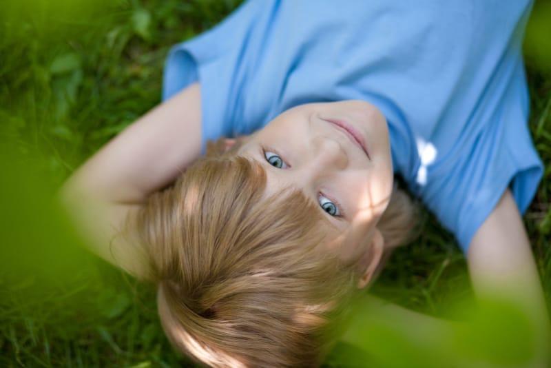 little boy in blue t-shirt lying on the grass