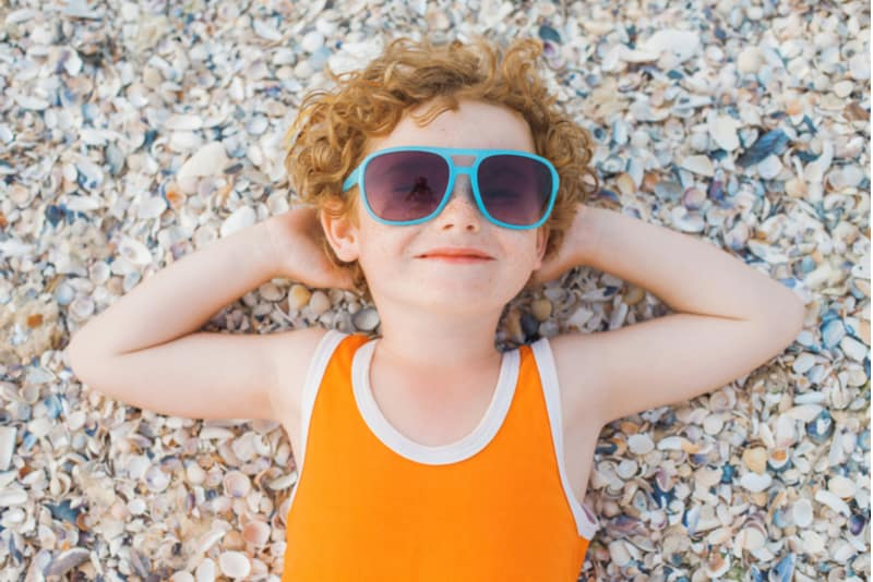 little curly-headed boy with blue sunglasses