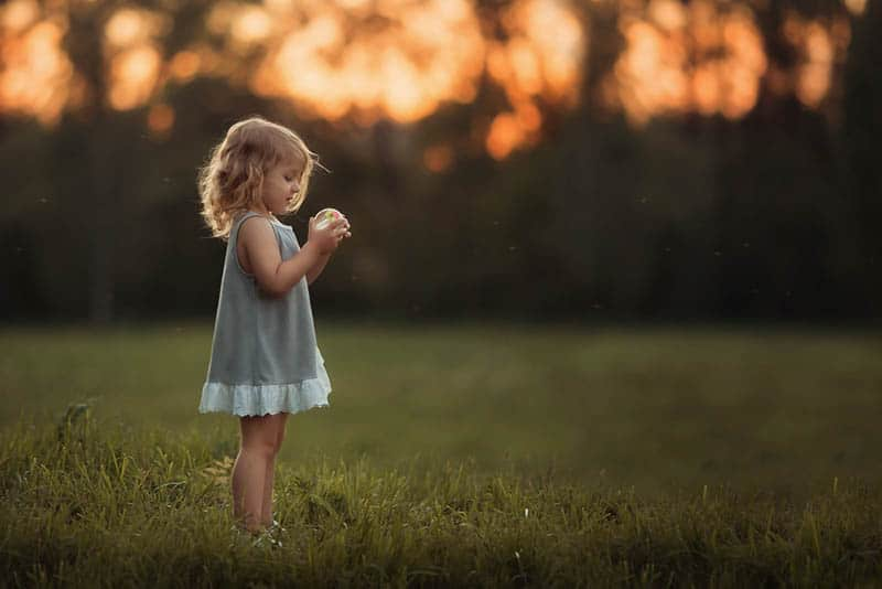 little girl playing with ball in the field