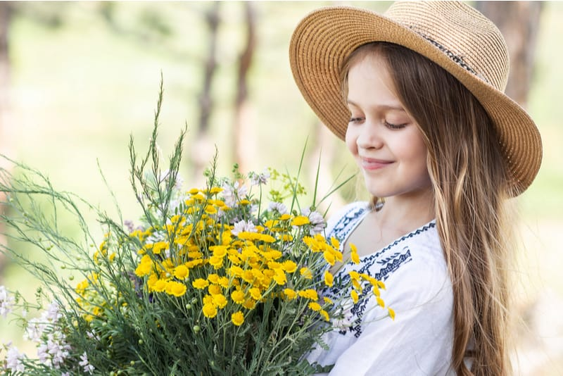 little girl wearing hat holding flowers in her hands