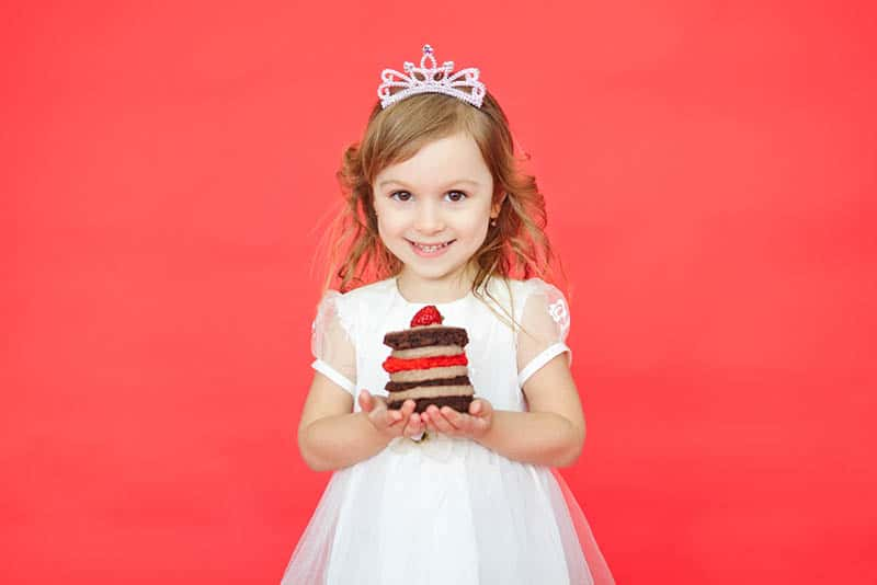 little girl with crown on the head holding a piece of cake