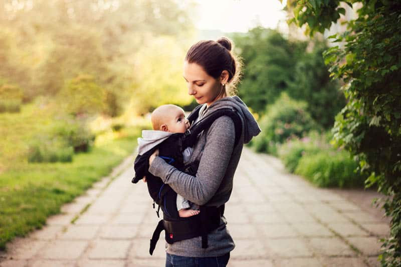 mother walking in the park with baby in carrier