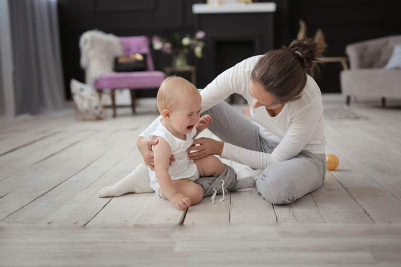 mother with crying baby on the floor