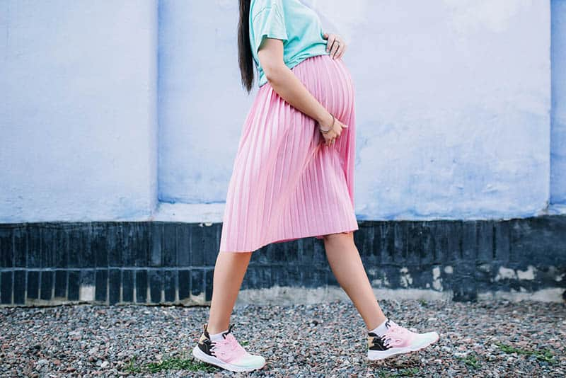 pregnant woman in pink skirt walking outdoor