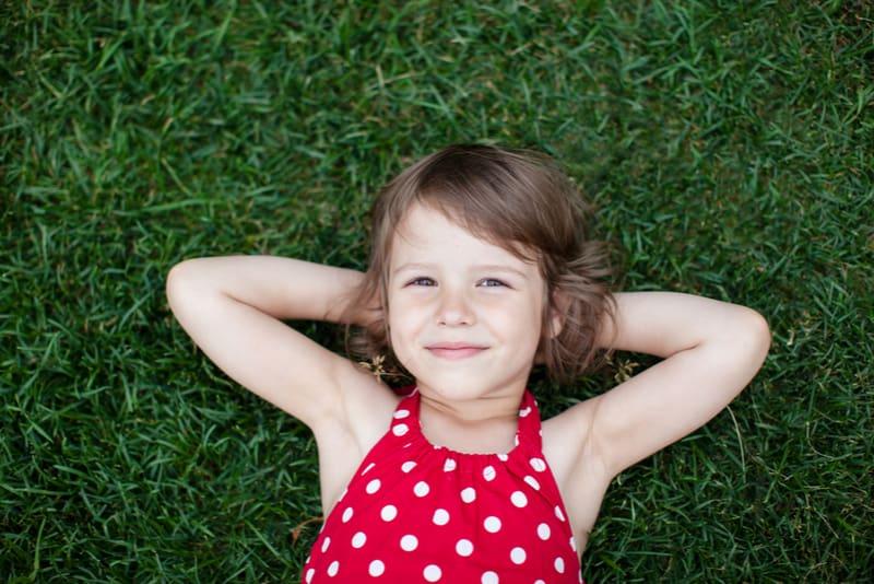 smiling little girl lying on green grass
