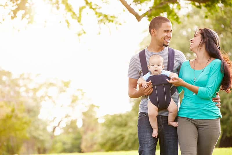 young parents walking in the park with baby in a carrier