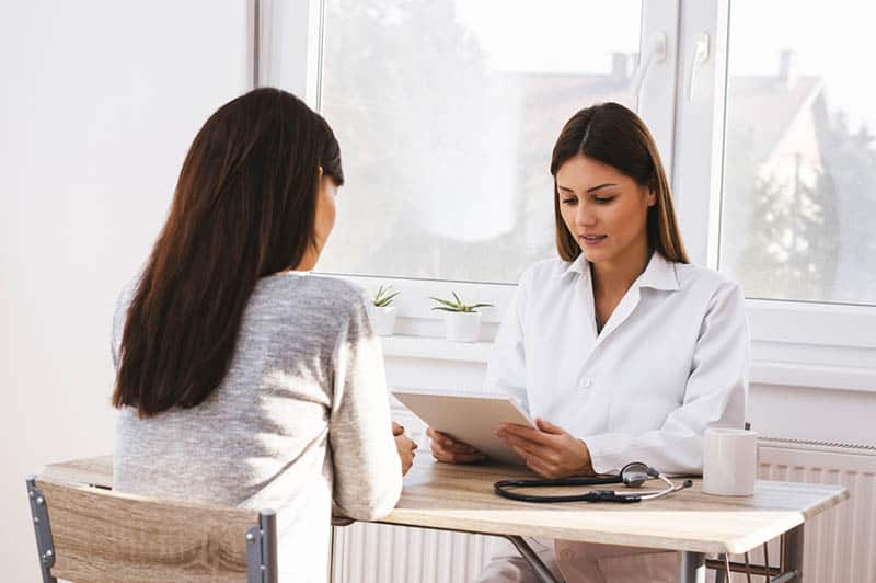 young woman talking with female doctor in the hospital office