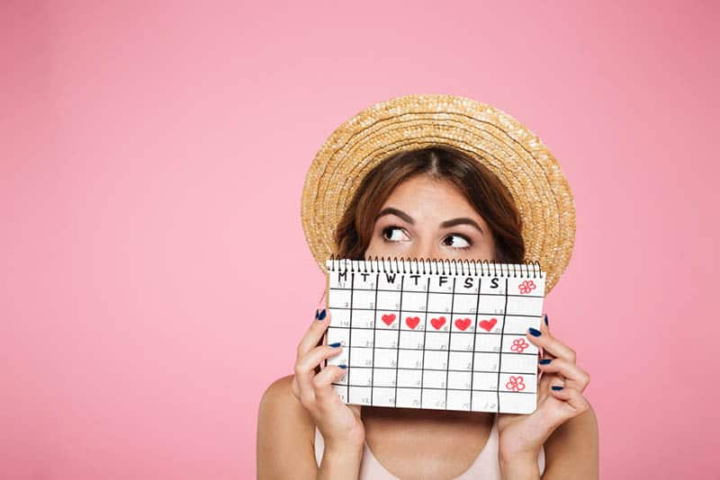 young woman with hat holding a period calender