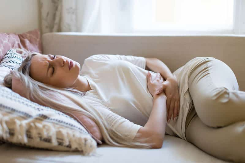 young worried woman feeling pain in stomach