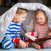 Two happy siblings reading books under the covers