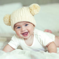 cute baby with winter hat lying on the bed