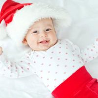 adorable baby smiling in Santa Claus suit