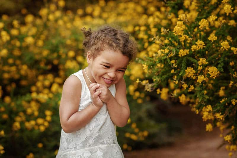 Happy little girl on the field of yellow flowers in summer