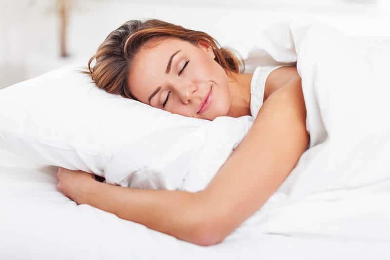 beautiful happy woman sleeping in bed