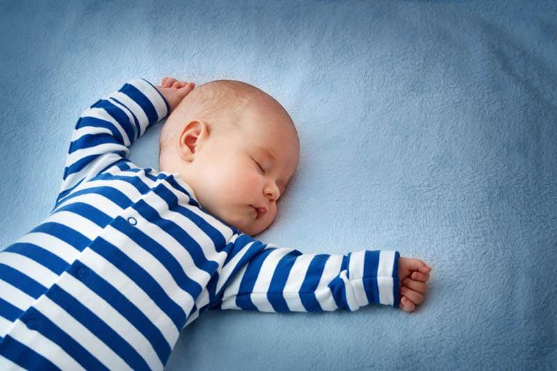 cute baby boy sleeping in bed