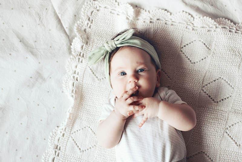 cute baby girl wearing headband lying on the crochet blanket
