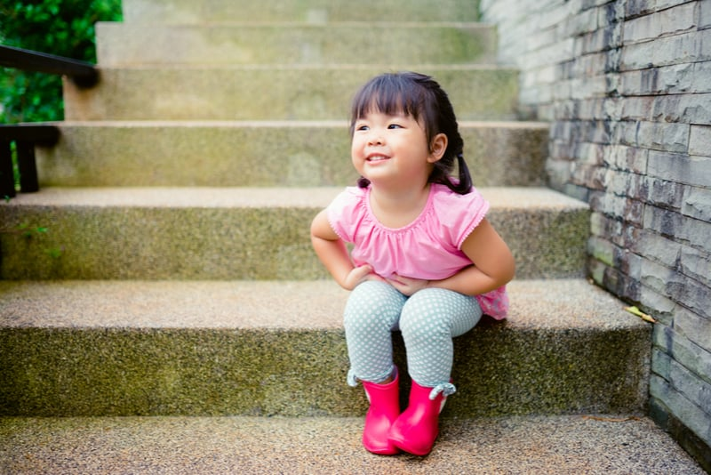 cute little asian girl sitting on the stairs