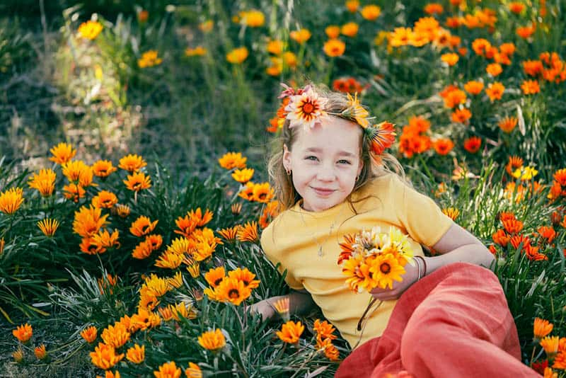 little girl posing in a meadow with flowers