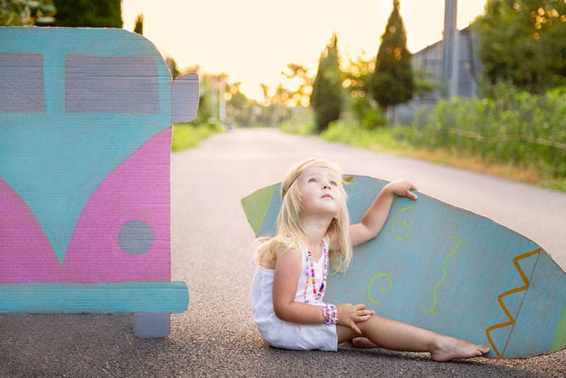little hippie girl sitting on the road and holding a surf