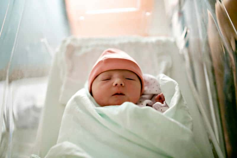 newborn baby with hat wrapped into blanket