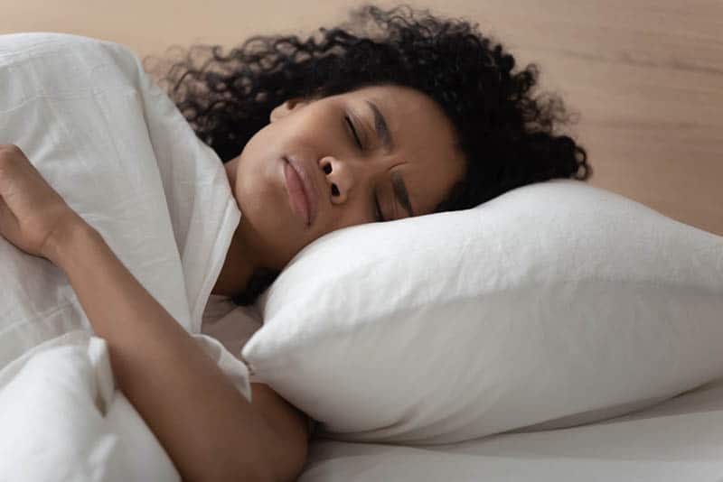 young woman having a nightmare while sleeping in bed